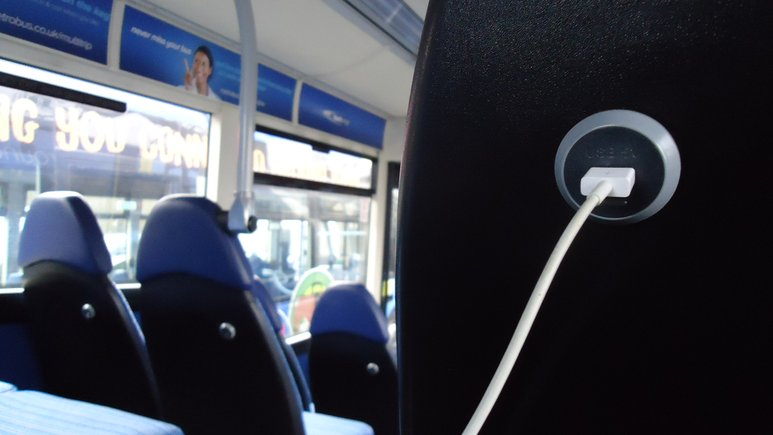 charging cable plugged into a usb point, situated on the back of a chair on the bus